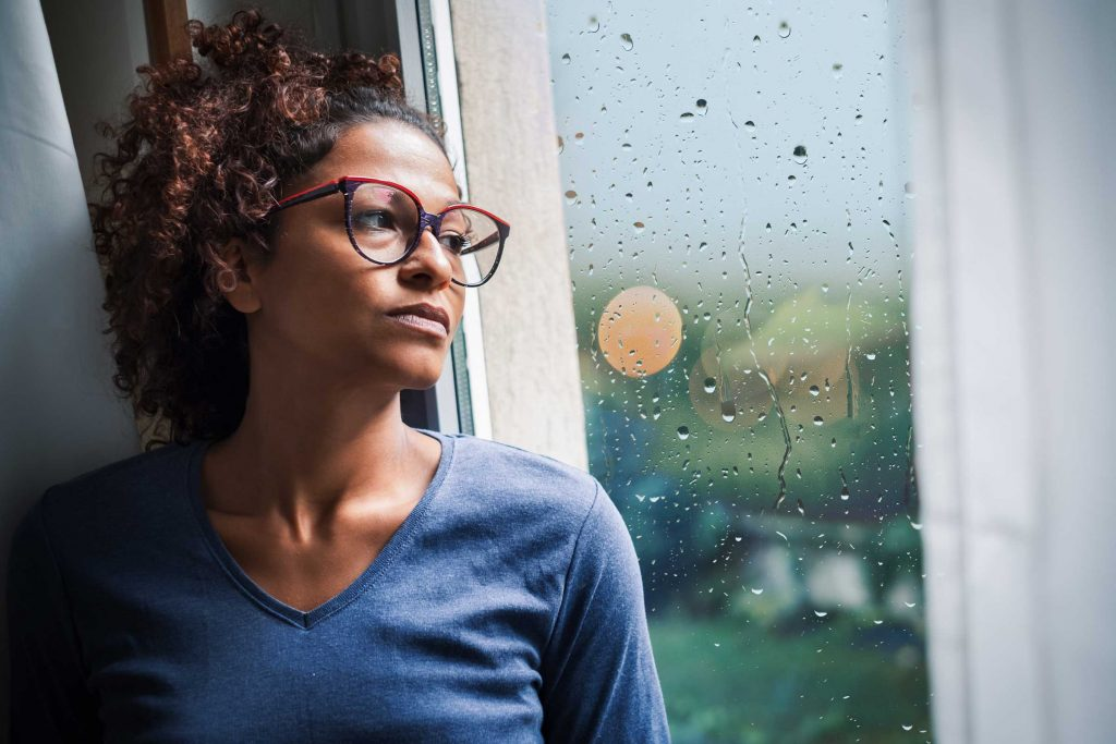 Sad person looking out window